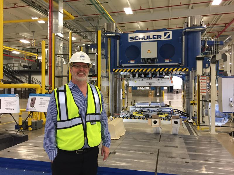 Dr. Ray Boeman stands in front of IACMI's compression press.