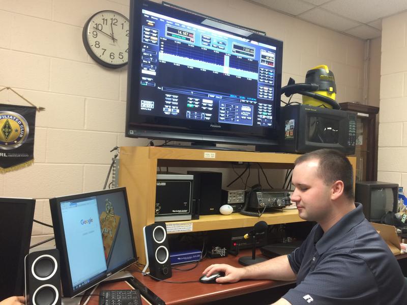 MSU Amateur Radio Club President Reece Cole sits in front of a digital radio display.