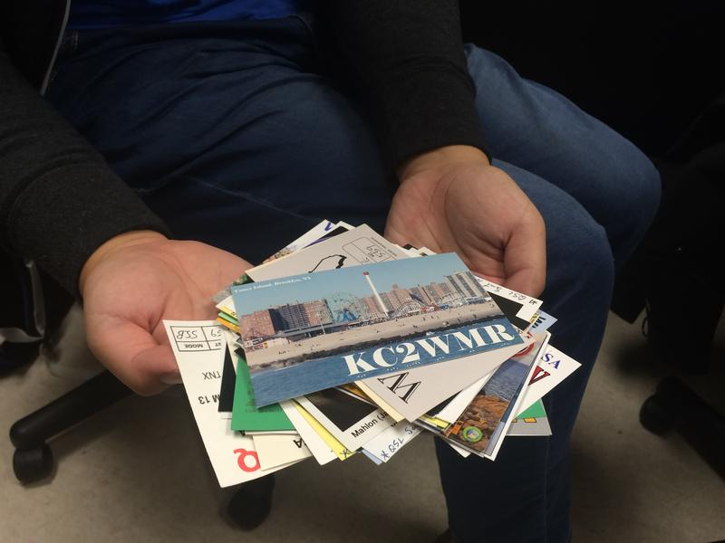 MSU Amateur Radio Club Vice President Teng Xu displays a collection of QSL cards from all over the world. A common practice among amateur radio enthusiasts is sending these cards to each other once they have made contact.