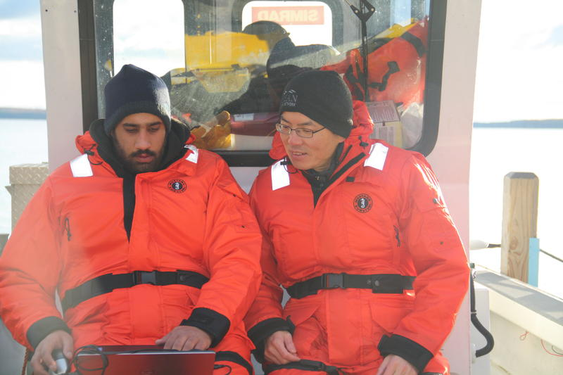 Osama Ennasar (L) and Xiaobo Tan on a boat.