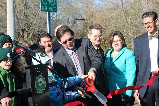 In this picture, Delhi Township manager John Hayhoe cuts the ribbon on a new nature trail.