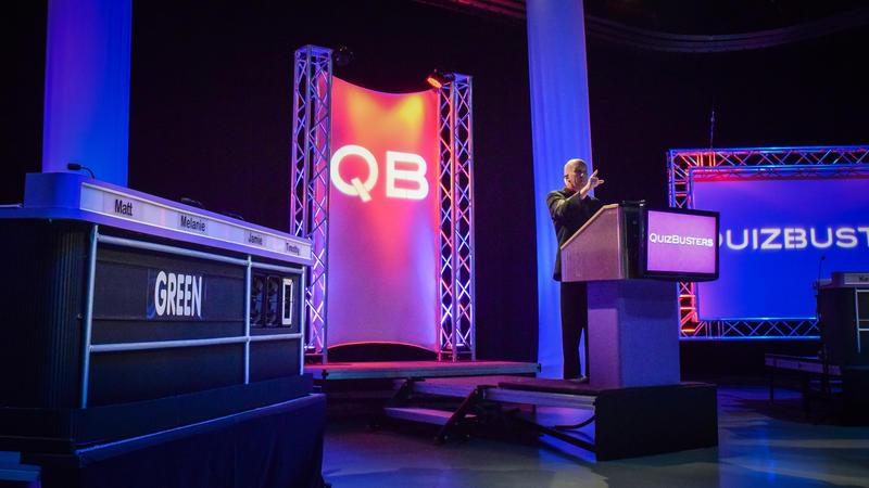 Ottinger at podium on QuizBusters set