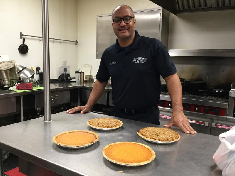 Lansing Fire Dept. Capt. David Odom Jr. standing with four fresh sweet potato pies.