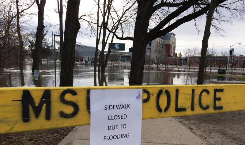 MSU police barrier at flooded sidewalk