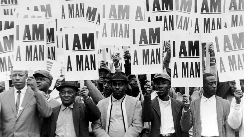 "Striking members of Memphis Local 1733 hold ""I Am a Man"" signs, the slogan that symbolized the sanitation workers 1968 campaign."