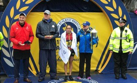 Desiree Linden (middle) poses for pictures after winning 2018 Boston Marathon.