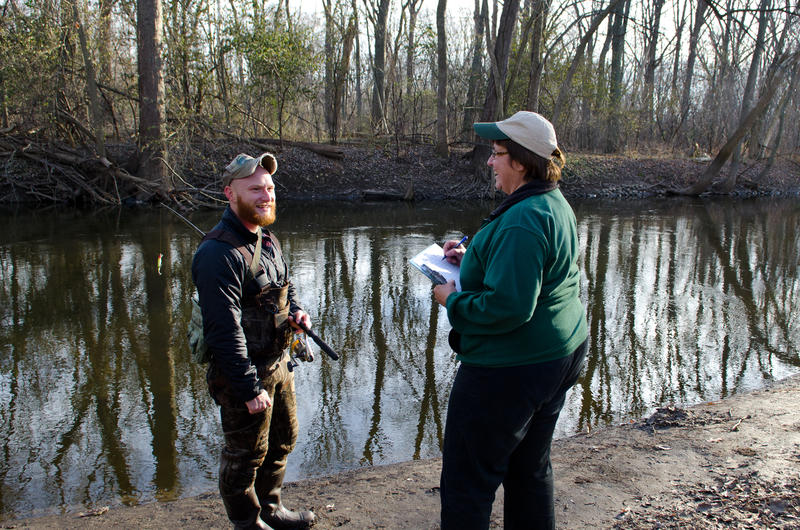An angler speaks with a DNR creel clerk.
