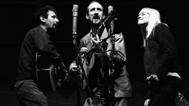 Three artists on stage singing