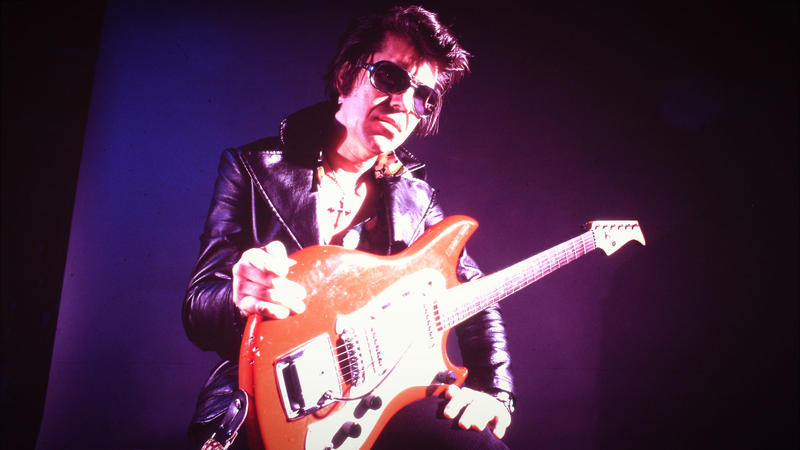 Link Wray with guitar on purple background.