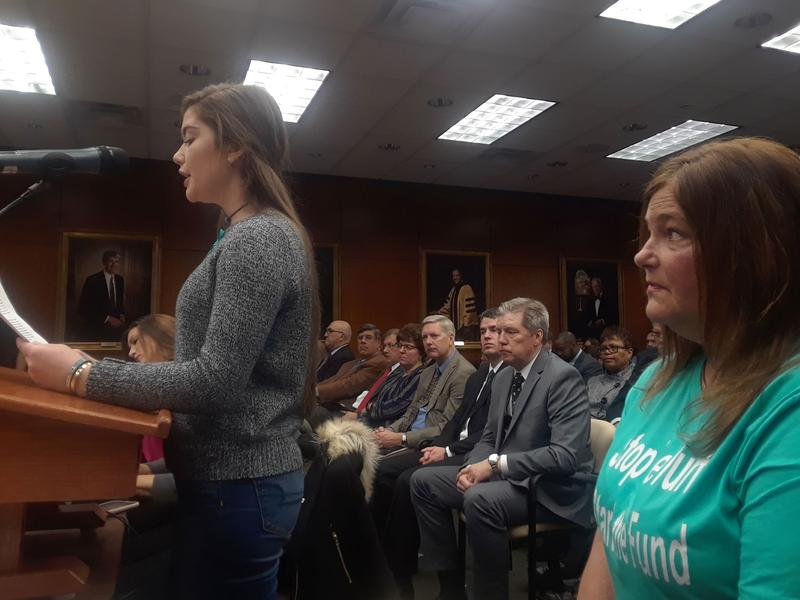 Emma Ann Miller, a 16 year old survivor, makes a public comment at the Board of Trustees meeting Friday while her mother Leslie Miller watches. The Millers oppose the school's decision to end the Healing Assistance Fund and transfer the money to a settlem