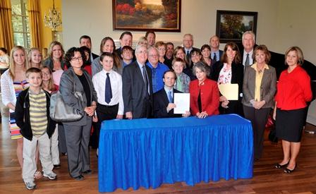 Lt. Gov. Brian Calley signs autism insurance bill with members of the Autism Alliance of Michigan.