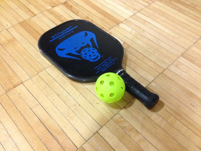Pickleball is played with a plastic ball and a paddle that resembles a ping pong paddle..