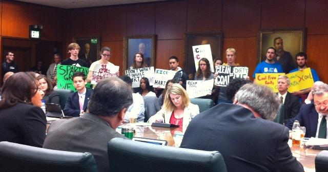"Students stand with signs with messages including ""Clean Coal=Dirty Lie"" and ""Coal Free Is Really Spartan Green"" at today's MSU Board of Trustees meeting."