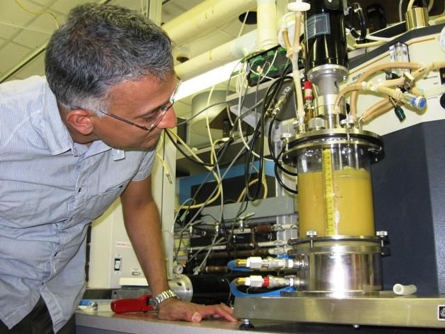 Michigan Biotechnology Institute (MBI) CEO Bobby Bringi studies a 1-liter sized fermentation vessel containing various sugars and minerals.  Substances like this create many usable products, including the food agent fumaric acid.
