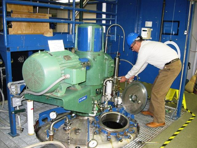 MBI Vice President of Engineering David Senyk opens a hatch to a large fermentation chamber.  During the scale-up process, bio-based compounds that were once tested in a smaller lab are measured for their effectiveness on a much larger scale.
