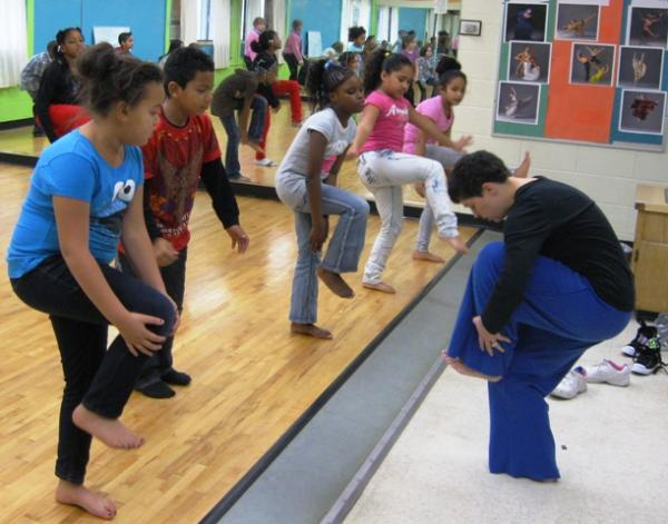 Dance instructor Heather Vaughn-Southard (right) leads third-grade students through an exercise at Pleasant View Visual and Performing Arts Magnet School in Lansing.