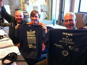 "Photo left to right: WKMS Program Director Tracy Ross, Asia Burnett and Roger Reichmuth display this fall's ""Feeding Hungry Minds Sounds Good"" logo tee."