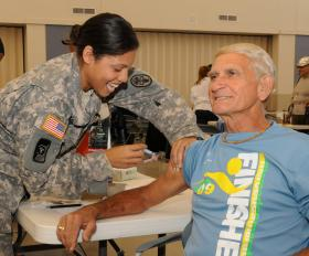 U.S. Army Captain Sharika Labrie from Blanchfield Army Community Hospital administers a flu vaccine to retired U.S. Army Chief Warrant Officer 3 Troy Johnson during Retiree Appreciation Day in 2010. In 2004, BACH had to quit seeing retirees on a regular basis because so many doctors and nurses were deployed.