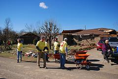 Aid workers and ordinary citizens work together in the aftermath of the tornado that tore through Muhlenberg County last February.