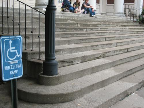 A handicap sign near <br>a large flight of stairs <br> on Murray State's <br>campus. The ramp <br> is around the corner.