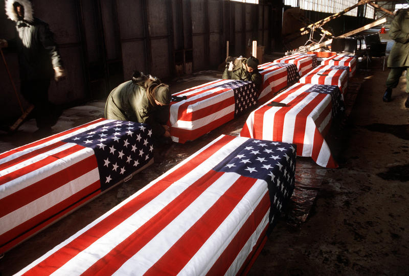 Soldiers fasten flags to caskets containing the remains of members of the 3rd Bn., 502nd Inf., 101st Airborne Div., while working in a temporary morgue at Gander Airport on Dec. 17th, 1985.