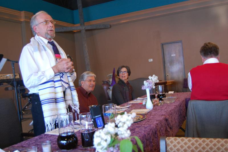 David Hannigan begins the Seder at Murray Family Church as pastor Butch Seargent and his wife Jan Seargent sit by his side.