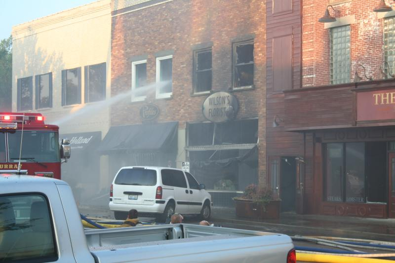 Firefighters work to contain the fire from 5th Street