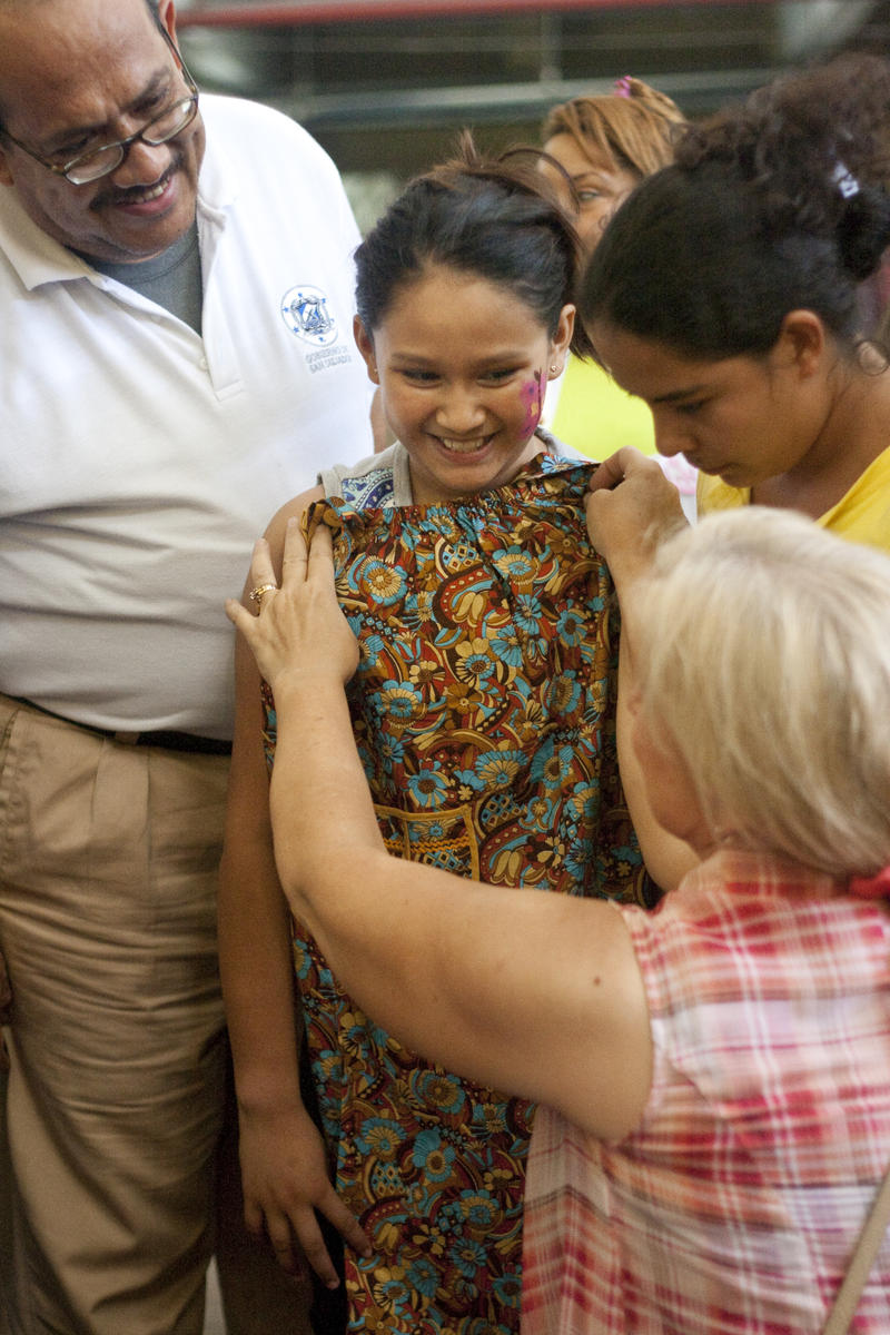 Laura Roberts gives a dress to a young girl in San Salvador, El Salvador. For the past 10 years, Laura has been taking volunteers from the United States on aid trips to help the poor and needy in El Salvador and other countries.