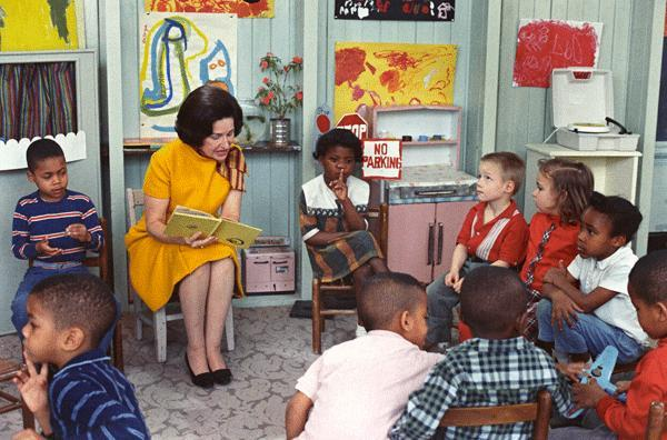 Lady Bird Johnson, the First Lady, reading to children enrolled in Project Head Start at Kemper School in Washington, DC. 1966.
