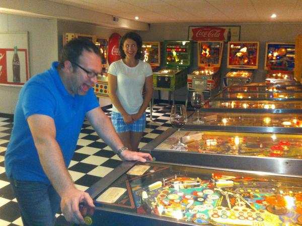 Duff bangs out a game on one of his many machines, with a glass of wine and his wife, Laura in the background.