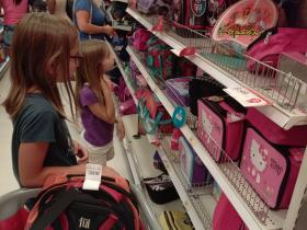 Somerset and her younger sister Genevieve try to pick out the right backpack for the right amount of books.
