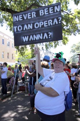"Volunteer Linda Berryman holds up a sign promoting Opera Memphis' ""30 Days of Opera."""