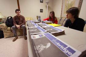 Jim Ekenstedt, left, talks with other volunteers who distribute the papers for the homeless to sell.