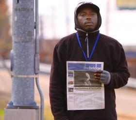 With his blue vendor's badge, Andre Ervin sells the papers for $1 that he bought for a quarter apiece.