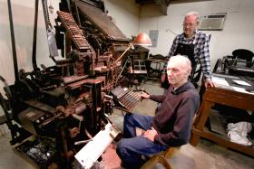 Ben Murdock (seated) and Johnny Tritt enjoy visiting the printing press at Green Frog Village.