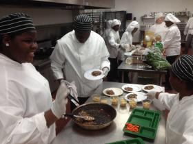 Students prepare a Salisbury Steak for plating.