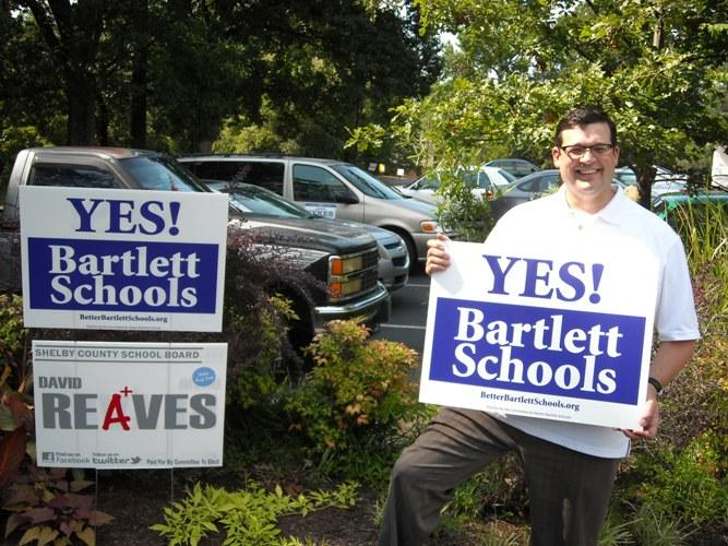 Candidate for Bartlett Alderman Jason Sykes plants a sign outside the Bethel Church early voting site. Sykes would like to see Bartlett form a separate school district.