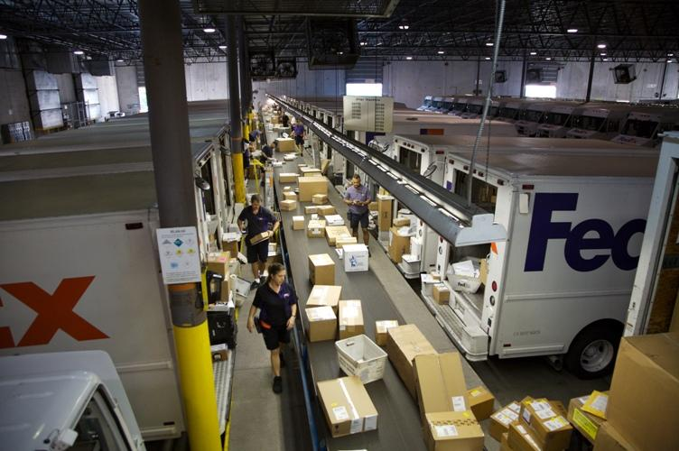 FedEx Express couriers pull packages off a conveyor belt .