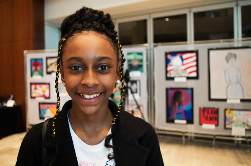 5th grader K'Teria of Bruce Elementary stands among artwork created by fellow students in the Shelby County School district.