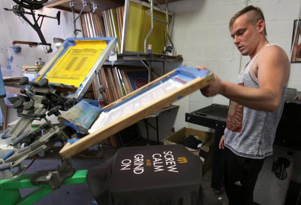 Monday, May 27, 2013 – Graphic artist Eric Evans finishes another silk-screened tee-shirt in the clothing store SACHË, which had boom times during the 2013 Western Conference Playoffs.
