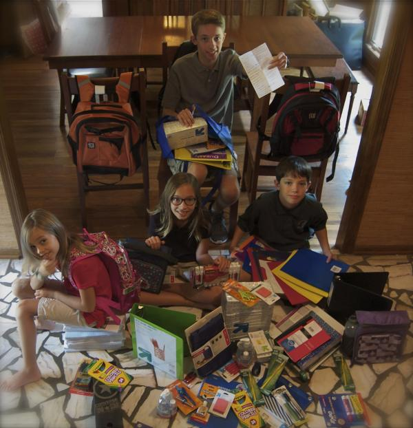 Calvin (in the chair), along with Genevieve, Somerset and Joshua Alley look over the bounty from their back-to-school shopping spree.