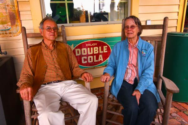 John and Nancy Freeman sit outside the first building they brought to Green Frog Village, a general store that is now a popular barbecue restaurant on Thursdays through Sundays.