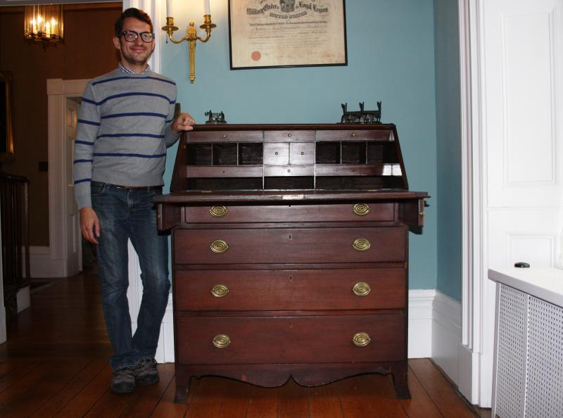 Ted Mallison is a curator at the Summit County Historical Society. He's standing next the the stand up secretary desk used by Akron founder Simon Perkins.
