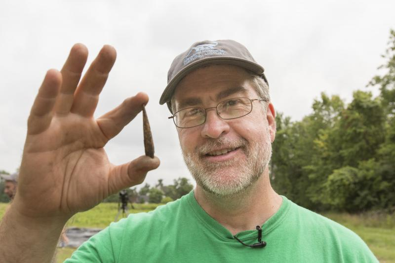 Brian Redmond, head of archaeology at the Cleveland Museum of Natural History, holds a spear point found at a 4,000 year-old site in Sheffield Village.