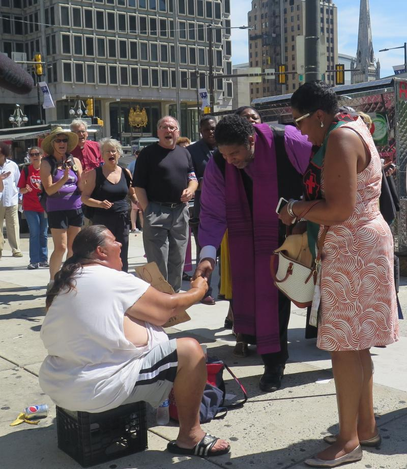 Faith leaders reach out to a homeless woman during the Democratic National Convention in Philadelphia