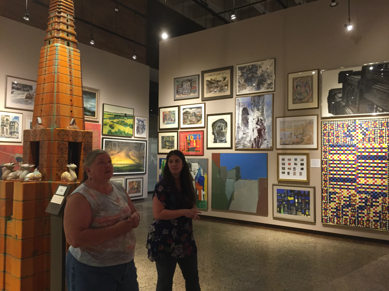 Chief Curator Lynnda Arrasmith and Assistant Registrar Kaleigh Pisani-Paige discuss the salon-style exhibit.