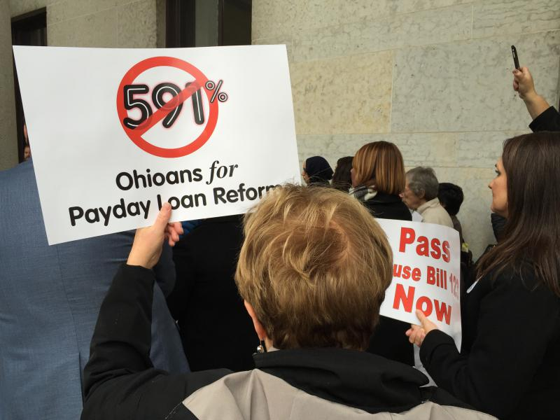 A photo of signs being held at a payday lending reform rally