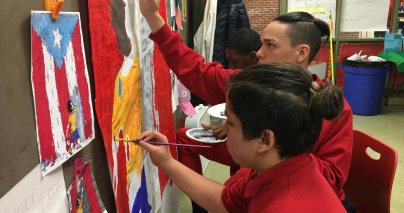 A photo of Isaiah Butchart and his classmates practicing painting the mural they'll paint in a Puerto Rican elementary school when they travel to the island to volunteer over their spring break.