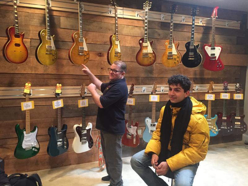 Lay's Guitar Shop Co-Owner Joel Shinn shows his custom guitars to national touring musician Ray Goren