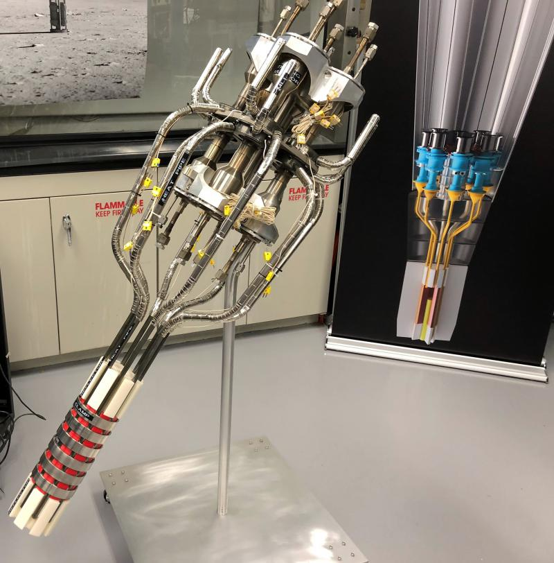 A full-scale model of the Kilopower system stands in front of a color diagram of the system.  It's the first time a Stirling engine has been placed on top of a nuclear reactor.